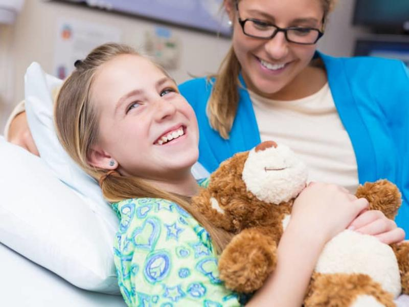 girl holding a teddy bear and smiling after her surgery with her mom nearby