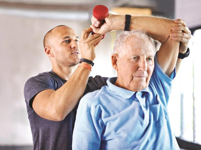 elderly male working with a physical therapist lifting weights