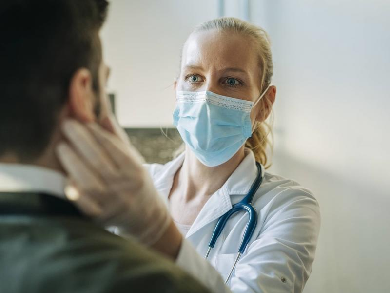 female physician examining a patient, while wearing a mask