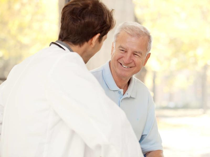 elderly male smiling while speaking with a doctor