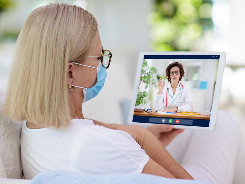 Masked woman telemed appt with doctor on ipdad
